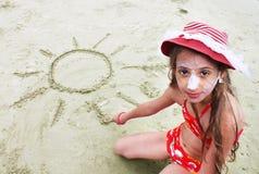 Schönes kleines Mädchen mit rotem Hut zeichnet die Sonne im Sand Stockfoto