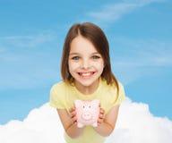 Schönes kleines Mädchen mit Sparschwein Stockbilder