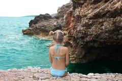 Schönes kleines Mädchen sitzt auf dem felsigen Strand Stockfotografie