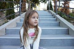 Schönes kleines Mädchen sitzt auf der Treppe Stockfotos