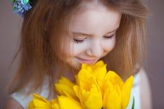 Schönes kleines Mädchen, welches das Aroma des Blumenstraußes der frischen Tulpen riecht Frühling und Sommerporträt der netten Ki Lizenzfreie Stockfotografie