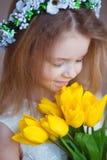 Schönes kleines Mädchen, welches das Aroma des Blumenstraußes der frischen Tulpen riecht Frühling und Sommerporträt der netten Ki Lizenzfreie Stockbilder