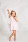 Schönes kleines Mode-Modell auf weißem Studiohintergrund Porträt des netten Mädchens aufwerfend im Studio Stockfotografie