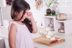Schönes kleines nahöstliches Mädchen, das in der Küche, Risse der Zwiebel schreit Schönes Tanzen der jungen Frau der Paare Stockbild