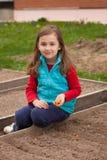 Schönes kleines russisches Mädchen, das auf Bretterzaun Of Bed Of sitzt lizenzfreie stockbilder