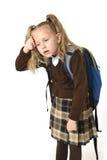 Schönes kleines Schulmädchen ermüdete und erschöpfte das Weitermachen ihres hecklastigen Schulrucksacks, der traurig schaut Stockfotografie