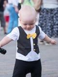 Schönes Kleinkind, das mit seiner Mutter an einem Stadtfeiertag geht Kinderstilvoll gekleideter Schmetterling und -kappe Jungenho Lizenzfreies Stockbild