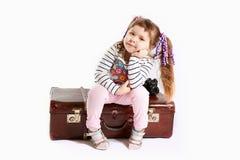Schönes Kleinkindmädchen, das auf Retro- Koffer sitzt Lizenzfreie Stockbilder