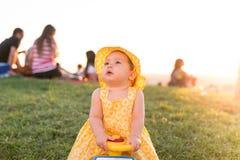 Schönes Kleinkindmädchen, das draußen auf einem Spielzeugauto sitzt stockfotografie