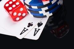 Schönes Konzept von Spielkarten und von den roten Würfeln für Poker auf einer dunklen Tabelle stockbild