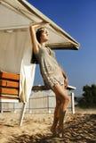 Schönes Kurzschlusskleid des jungen Mädchens, das auf Sand unter einem Regenschirm steht Lizenzfreies Stockfoto