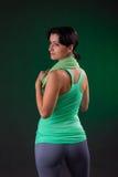 Schönes Lächeln athletisch, Eignungsfrauenstellung, werfend mit einem Tuch auf einem grauen Hintergrund mit einer grünen Hintergr Stockfotos