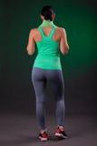 Schönes Lächeln athletisch, Eignungsfrauenstellung, werfend mit einem Tuch auf einem grauen Hintergrund mit einer grünen Hintergr Lizenzfreie Stockbilder