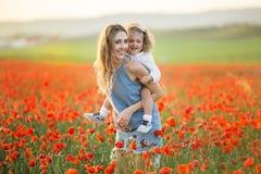 Schönes lächelndes Baby mit Mutter haben Spaß auf dem Gebiet von roten Mohnblumenblumen über Sonnenunterganglichtern, Frühlingsze lizenzfreie stockbilder