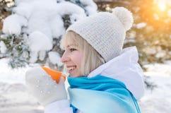 Schönes lächelndes blondes Mädchen in einem Sporthut, der eine Schale heißen Tee mit Dampf hält stockfoto