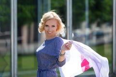 Schönes lächelndes blondes Modell, das mit flatterndem Halstuch aufwirft Stockbilder