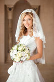 Schönes lächelndes Brautmädchen mit Blumenstrauß von Rosen in Hochzeitsdr. Lizenzfreie Stockfotografie