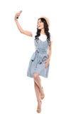 Schönes lächelndes Brunettemädchen im Strohhut und in Kleid, die selfie auf Smartphone nehmen Stockfotografie