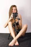 Schönes lächelndes Brunettemädchen mit einer Kamera sitzt auf einem weichen Boden Stockbilder