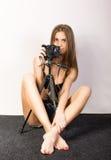 Schönes lächelndes Brunettemädchen mit einer Kamera sitzt auf einem weichen Boden Lizenzfreies Stockfoto
