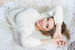 Schönes lächelndes glückliches Mädchen mit hellem Make-up liegt auf dem Bett mit Pelz in der weißen Strickjacke im Rahmen von Sch Stockfotos