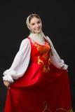 Schönes lächelndes kaukasisches Mädchen im russischen Volkskostüm Stockfotografie