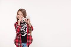 Schönes lächelndes Kindermädchen, das eine sofortige Kamera hält Lizenzfreies Stockfoto