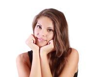 Schönes lächelndes Mädchen betrachtet Kamera und unterstützt Kinn durch Arme Stockfotografie