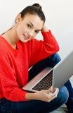 Schönes lächelndes Mädchen, das einen Laptop anhält. Stockfotos