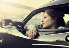 Schönes lächelndes Mädchen, das im Auto sitzt Stockbild