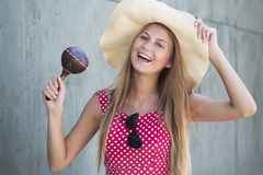 Schönes lächelndes Mädchen, das maracas und Hut hält Stockbilder