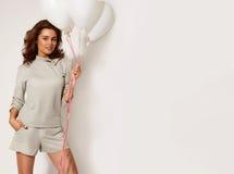 Schönes lächelndes Mädchen, das weiße Ballone auf einem weißen Hintergrund am Studio hält Stockbild