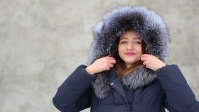 Schönes lächelndes Mädchen der Nahaufnahme, das blauen Mantel mit Pelzhaube im Winter, Schnee trägt stock video