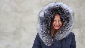 Schönes lächelndes Mädchen der Nahaufnahme, das blauen Mantel mit Pelzhaube im Winter, Schnee trägt stock footage