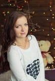 Schönes lächelndes Mädchen in der warmen weißen Jacke sitzt nahe dem Fenster nahe bei der Wand in den Lichtern Stockfoto