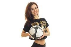 Schönes lächelndes Mädchen in einem Sporthemd hält den Ball und untersucht eine Kamera Stockbild