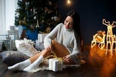 Schönes lächelndes Mädchen in einem weißen Pullover nahe chrismas Baum Lizenzfreie Stockfotos
