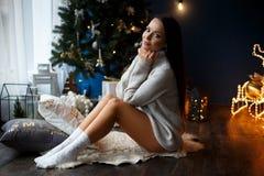 Schönes lächelndes Mädchen in einem weißen Pullover nahe chrismas Baum Stockbilder