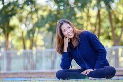 Schönes lächelndes Mädchen mit Sportkleidung sitzt und entspannendes i Lizenzfreies Stockfoto