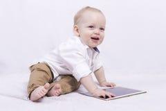 Schönes lächelndes nettes Baby mit einer Tablette Stockbild