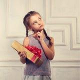 Schönes lächelndes nettes Mädchen, das den Goldkasten mit Geschenk mit rotem Bogen hält und oben schaut Lizenzfreies Stockbild