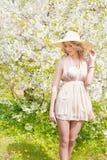 Schönes lächelndes süßes Mädchen mit dem langen blonden gelockten Haar, das einen Hut mit großen Feldern in Sommerrosa sundress t Lizenzfreie Stockfotografie