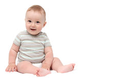 Schönes lachendes Baby, das auf Weiß sitzt stockbilder