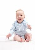 Schönes lachendes glückliches Baby, das auf Bett sitzt Lizenzfreie Stockfotos