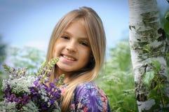 Schönes lachendes Mädchen auf einem Gebiet des Purpurs Stockfoto