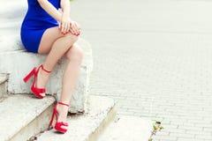 Schönes langes Beinmädchen in den roten Schuhen im blauen Kleid sitzt in der Stadt stockfoto