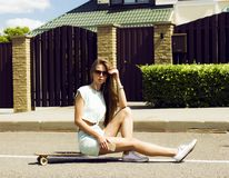 Schönes langhaariges Mädchen in der Sonnenbrille sitzt an Lizenzfreie Stockfotografie