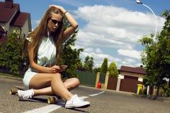 Schönes langhaariges Mädchen in der Sonnenbrille sitzt an Stockbilder