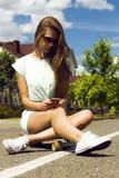 Schönes langhaariges Mädchen in der Sonnenbrille sitzt an Stockfoto