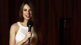 Schönes langhaariges Mädchenlächeln, Blicke auf Kamera und singt freundlich mit mic stock video